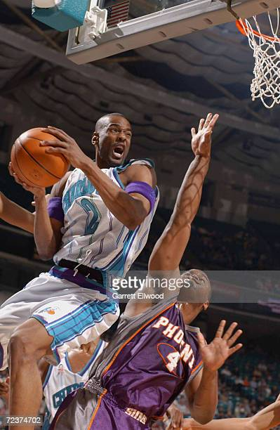 Stacey Augmon of the Charlotte Hornets glides to the basket against the defense of Alton Ford of the Phoenix Suns at the Charlotte Coliseum in...