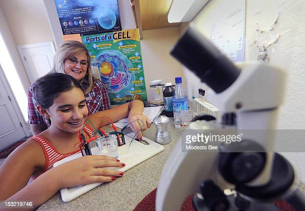 Stacey Gonzales top watches as her daughter Sabrinna works on her electrolyte experiment at their Oakdale home September 20 2012