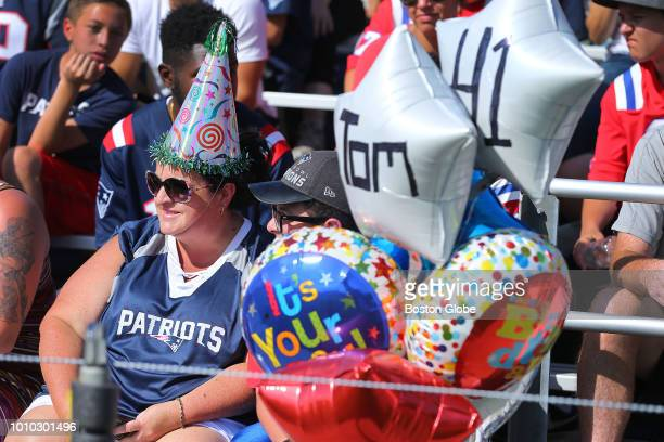 Stacey Lavingne from Dudley wears a birthday hat as she sits in the stands with balloons she brought in celebration of Patriots quarterback Tom...