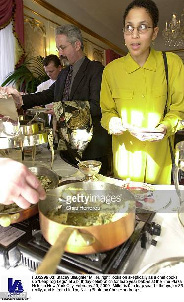 Stacey Slaughter Miller right looks on skeptically as a chef cooks up Leapfrog Legs at a birthday celebration for leap year babies at the The Plaza...
