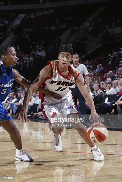 Stacey Thomas of the Portland Fire drives to the basket defended by Elaine Powell of the Orlando Miracle during the game on June 26 2002 at the Rose...