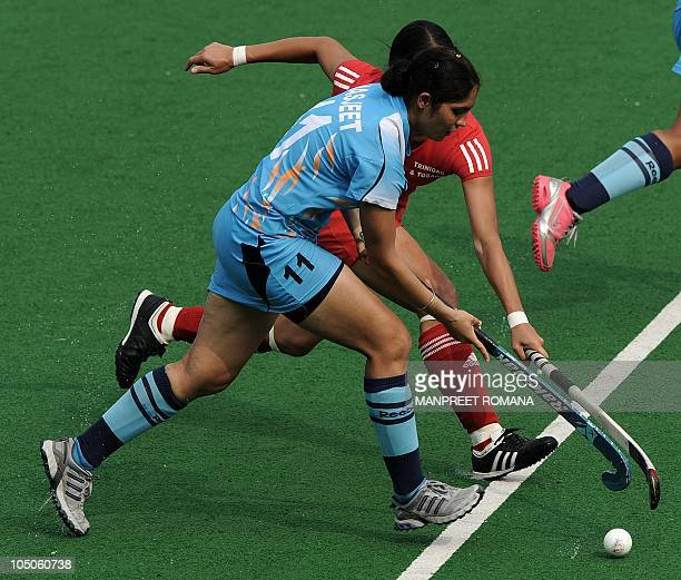 StaceyAnn Siu Butt of Trinidad and Tobago fights for the ball with Jasjeet Kaur Handa of India during their field hockey match at the Major Dhyan...