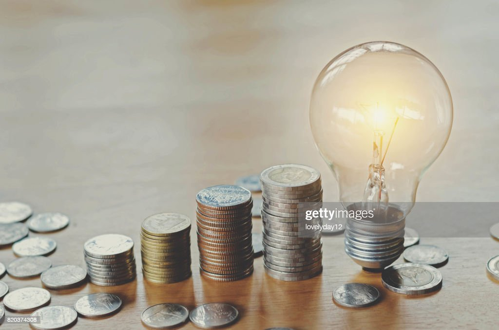 stack money coins with growing light bulb concept : Stock Photo
