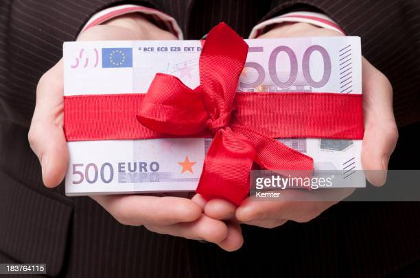 stack of 500 euro banknotes with red ribbon