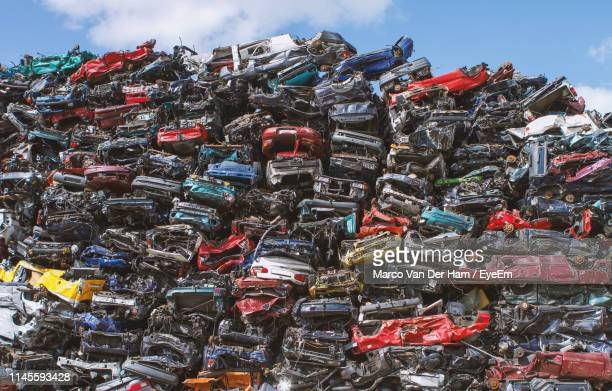 stack of abandoned cars outdoors - junkyard stock photos and pictures