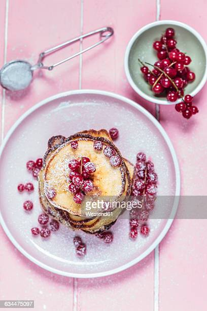 Stack of American pancakes with red currents sprinkled with icing sugar