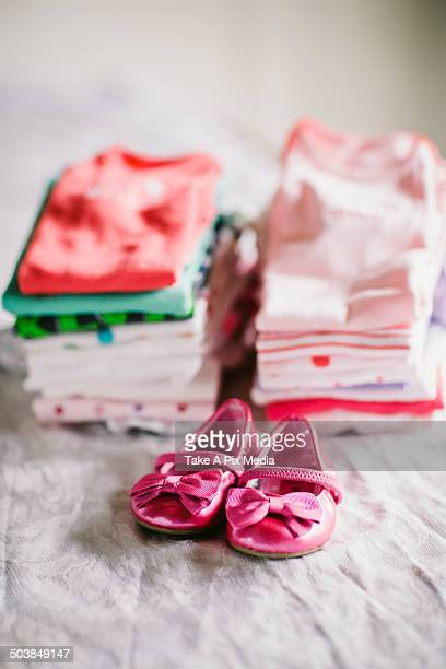 Stack of baby clothes with shoes