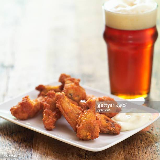 A stack of baked buffalo wings and a pint of lager