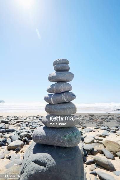 stack of balanced stones at beach against sea, blue sky and sun - 石塚 ストックフォトと画像