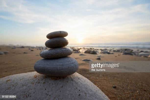 Stack of balanced stones at beach during sunset