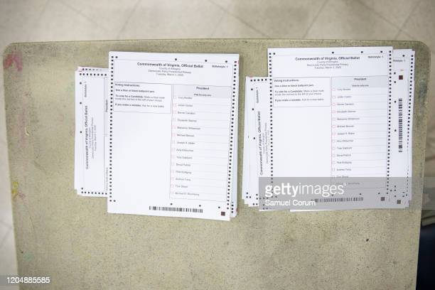 A stack of ballots for the Democratic presidential primary that still includes candidates that have withdrawn from the race are stacked on a table at...