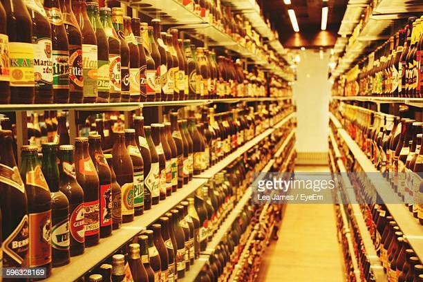 Stack Of Beer Bottles On Shelf At Shop
