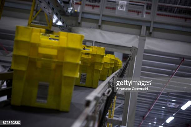 A stack of bins filled with inbound merchandise move along a conveyor belt at the Amazoncom MPX5 fulfillment center on November 17 2017 in Castel San...