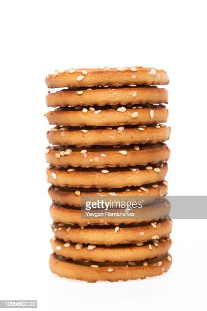 stack of biscuit cookies stack isolated on white background - cracker snack stock photos and pictures
