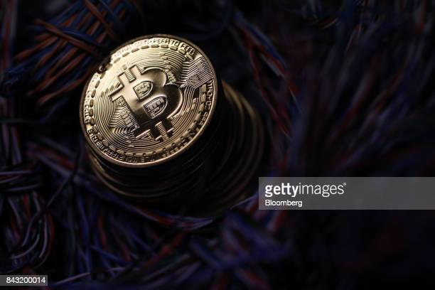 A stack of bitcoins sit among twisted copper wiring inside a communications room at an office in this arranged photograph in London UK on Tuesday...