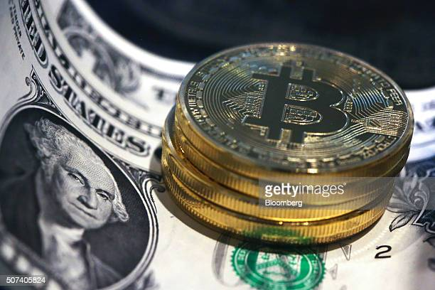 A stack of bitcoins stand on top of US one dollar bills in this arranged photograph in London UK on Friday Jan 29 2016 The International Monetary...