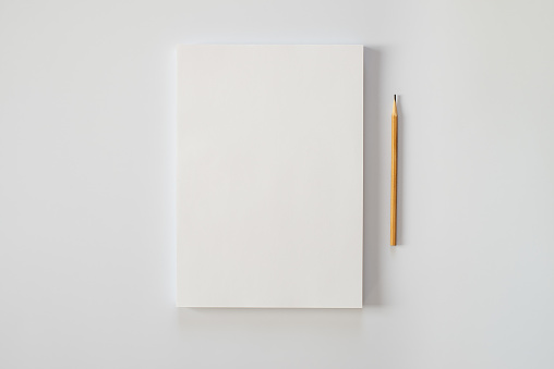 A stack of blank sheets of paper and a pencil on a white background. Creative crisis or the beginning of a new novel. 1133116965