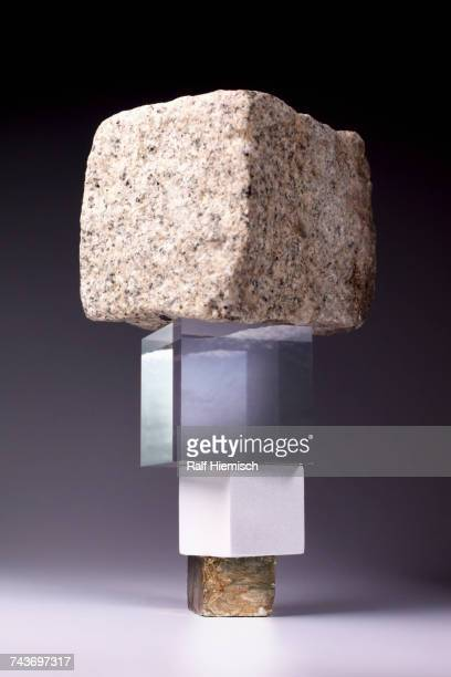 Stack of block shaped stones and glass boxes against gray background