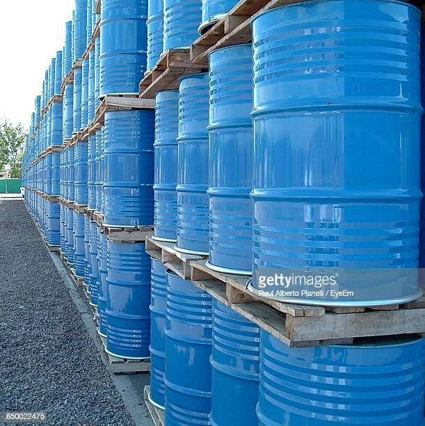 stack of blue oil drums on field - oil barrel stock pictures, royalty-free photos & images