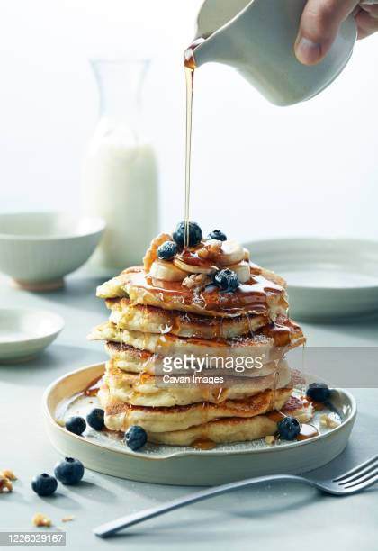 stack of blueberry banana walnut pancakes with syrup pouring breakfast - syrup stock pictures, royalty-free photos & images