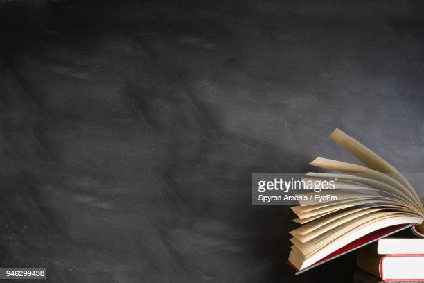 stack of books against blackboard - literature stock pictures, royalty-free photos & images
