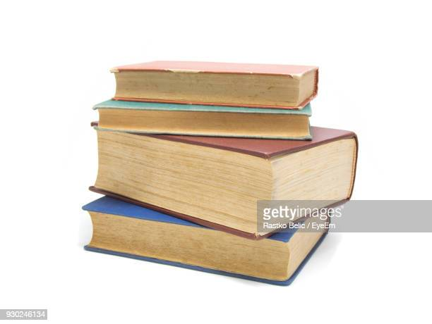 stack of books against white background - stack of books stock photos and pictures