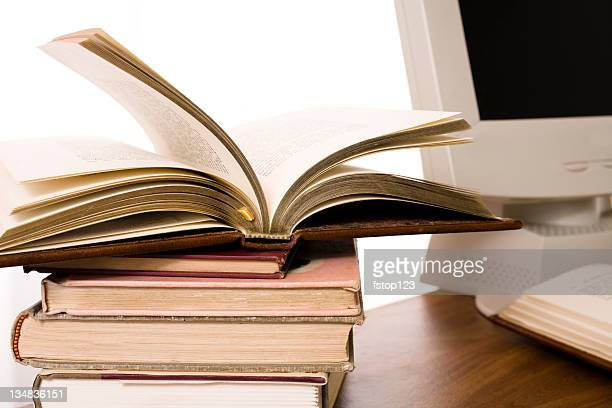 Stack of books beside computer on desk