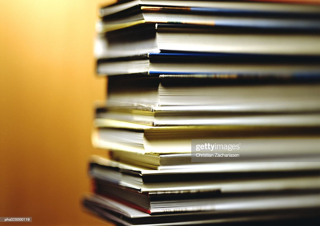 Stack of books, corners in foreground, yellow background : Foto de stock