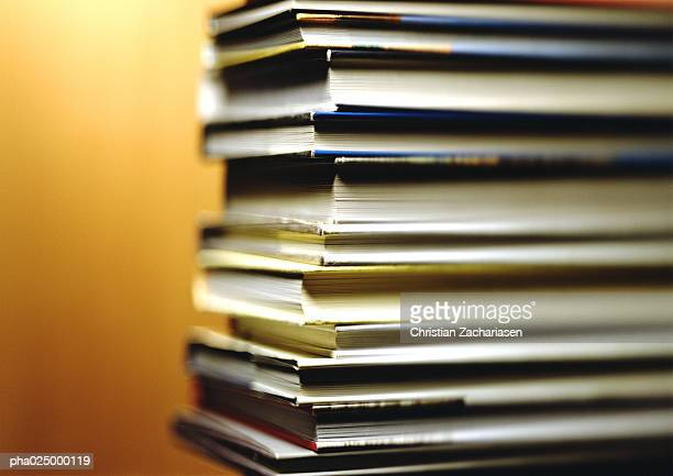 Stack of books, corners in foreground, yellow background