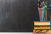 A stack of books, glasses, pencils on the background of a black school board. The concept of education. Copy space.