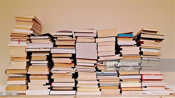 Stack Of Books On Table Against Beige Wall