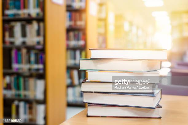 stack of books on table in library - textbook stock pictures, royalty-free photos & images