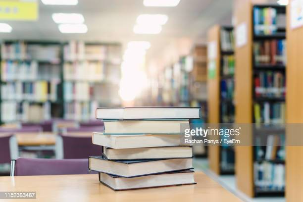 stack of books on table in library - library stock pictures, royalty-free photos & images