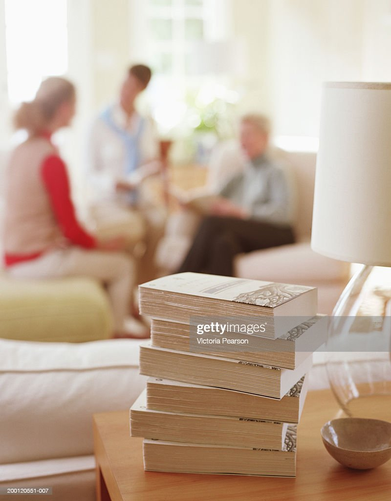 Stack of books sitting on table in living room, women in background : Stock Photo