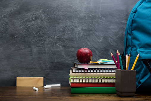 Stack of books, stationery and education supplies on wooden desk 947648828