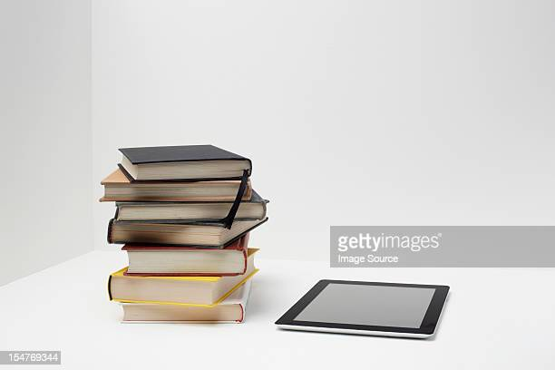 Stack of books with digital tablet