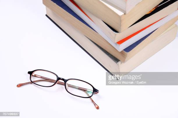 Stack Of Books With Eyeglasses On White Background