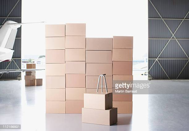 stack of boxes and hand truck in hangar - dolly martin stock photos and pictures