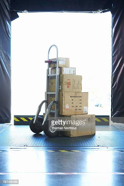 stack of boxes on sack barrow in loading bay - sack barrow stock pictures, royalty-free photos & images