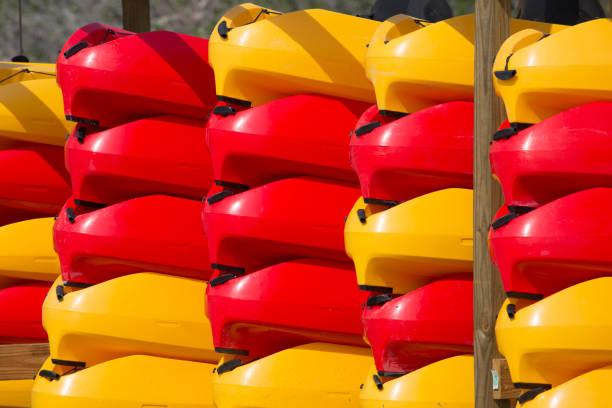 Stack of bright red and yellow kayaks on the shore of Florida Bay, Flamingo, Everglades National Park, Florida, USA