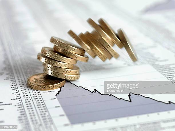 stack of british pound coins falling on list of share prices - decline stock pictures, royalty-free photos & images
