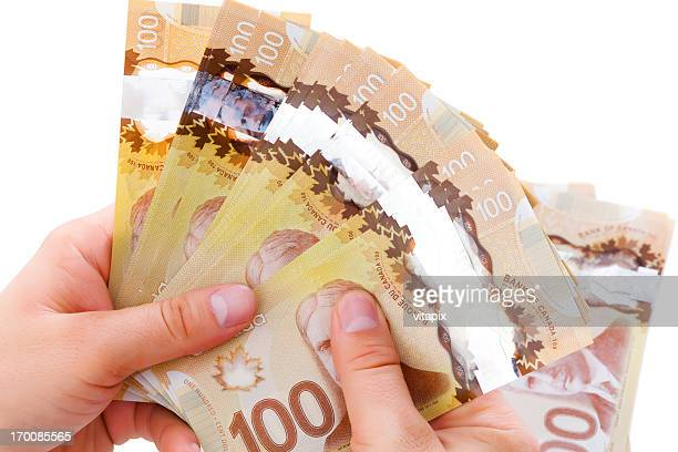 stack of canadian $100 bills in man's hands - canadian currency stock pictures, royalty-free photos & images