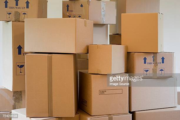 stack of cardboard boxes in a room - cardboard box stock pictures, royalty-free photos & images