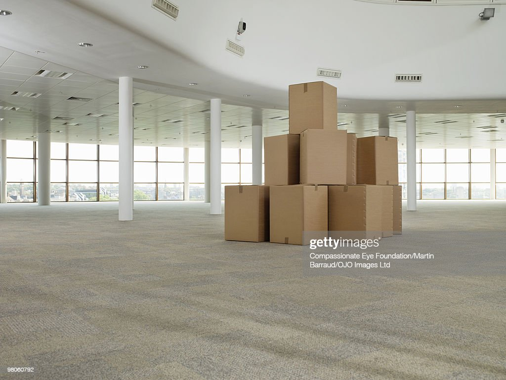 stack of cardboard boxes in middle of empty room : Stock Photo