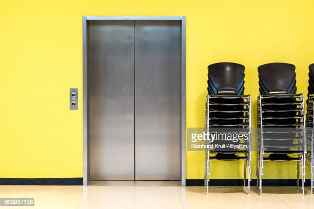 Stack Of Chairs By Elevator Against Yellow Wall In Building