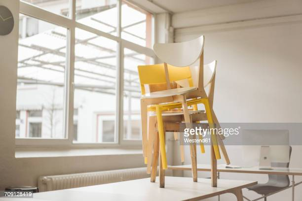 Stack of chairs standing on meeting table in a loft