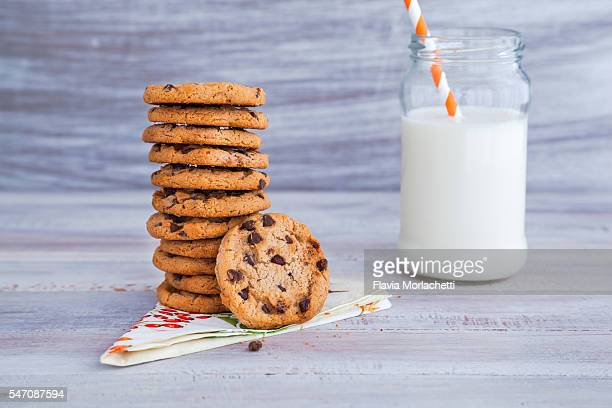 Stack of chocolate chip cookies and a jar with milk