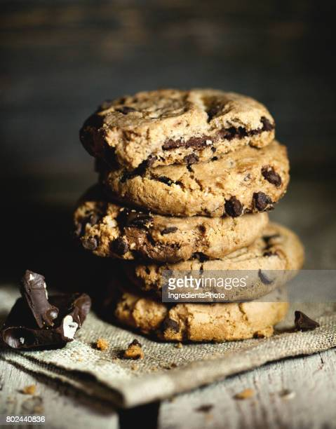 Stack of chocolate chip cookies and chocolate on wooden table.
