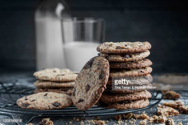 stack of chocolate chip cookies with a glass of milk in the background on rustic background. - tina terras michael walter stock-fotos und bilder