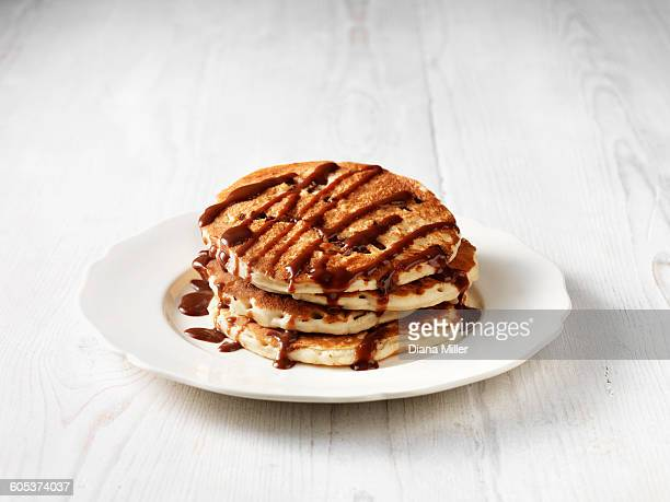 Stack of chocolate chip pancakes drizzled with chocolate sauce